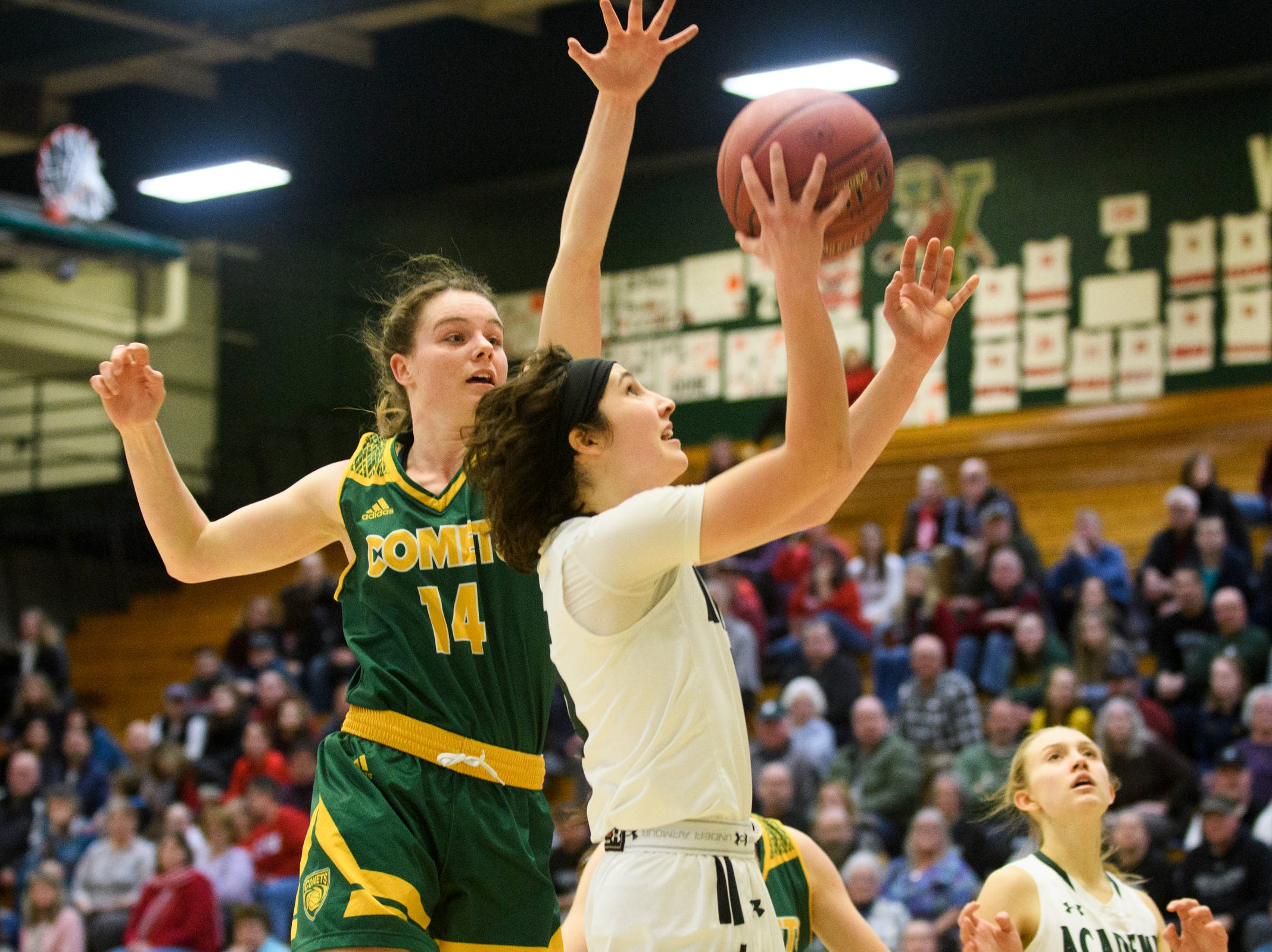 St. Johnsbury's Sadie Stetson (5) leaps for a lay up past BFA's Caitlyn Dasaro (14) during the girls semifinal basketball game between the BFA St. Albans Comets and the St. Johnsbury Hilltoppers at Patrick Gym on Wednesday night March 6, 2019 in Burlington, Vermont.