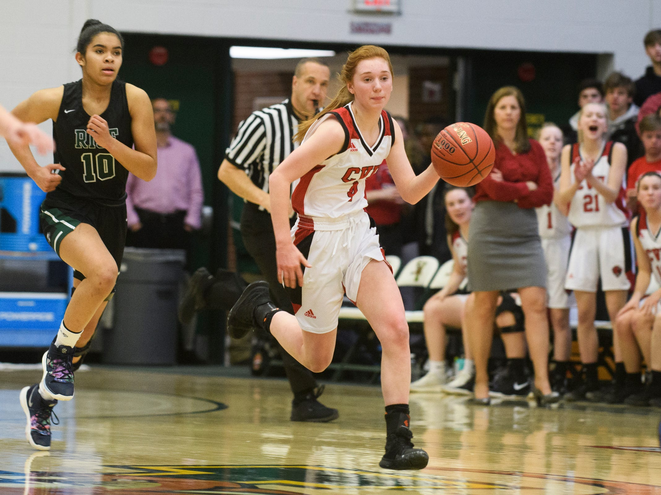 CVU's Catherine Cilwee (4) dribbles the ball down the court during the girls semifinal basketball game between the Rice Green Knights and the Champlain Valley Union Redhawks at Patrick Gym on Wednesday nigh March 6, 2019 in Burlington, Vermont.
