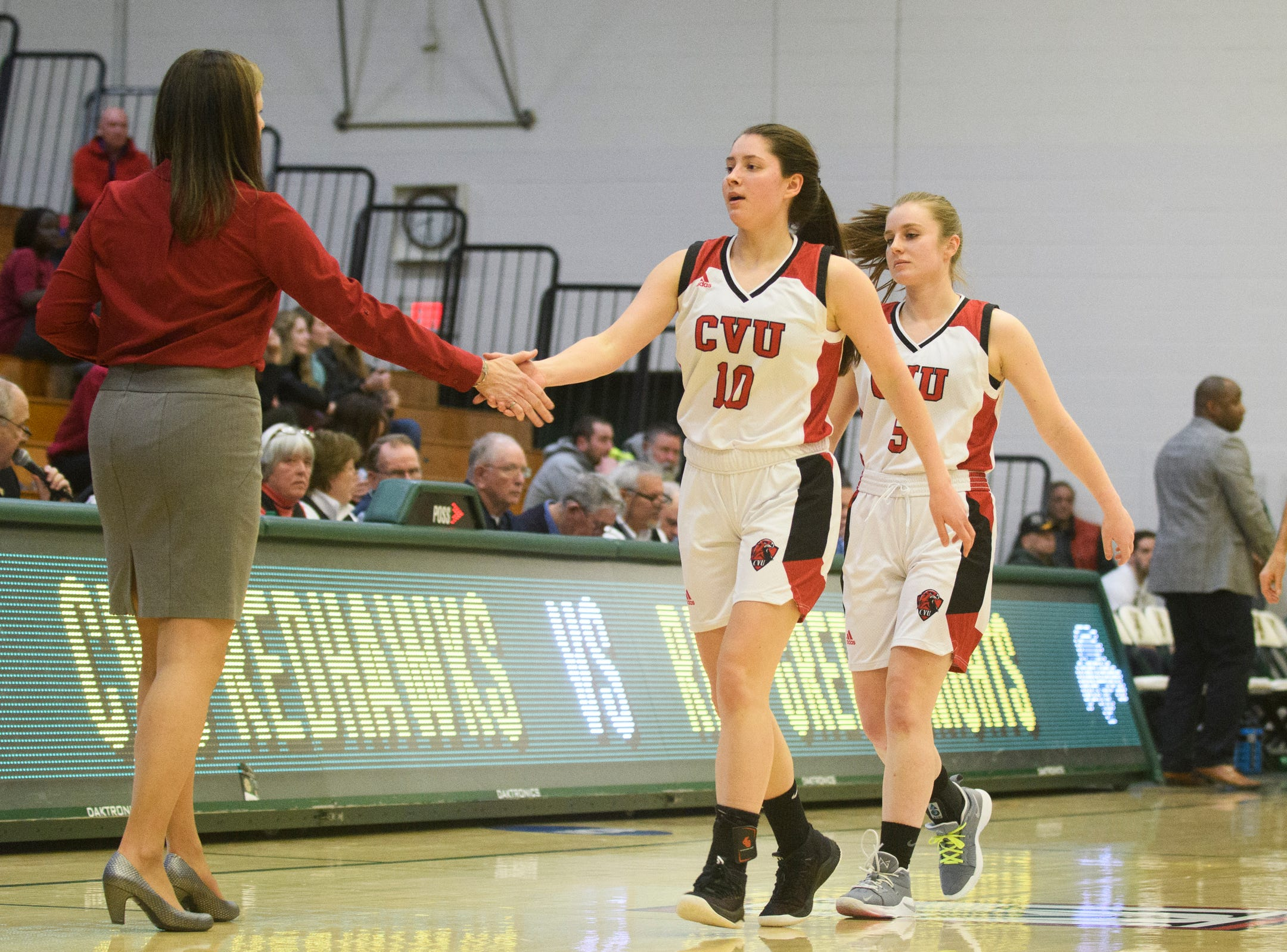 CVU's Quinn Boardman (10) high fives head coach Ute Otley as she heads to the bench during the girls semifinal basketball game between the Rice Green Knights and the Champlain Valley Union Redhawks at Patrick Gym on Wednesday nigh March 6, 2019 in Burlington, Vermont.