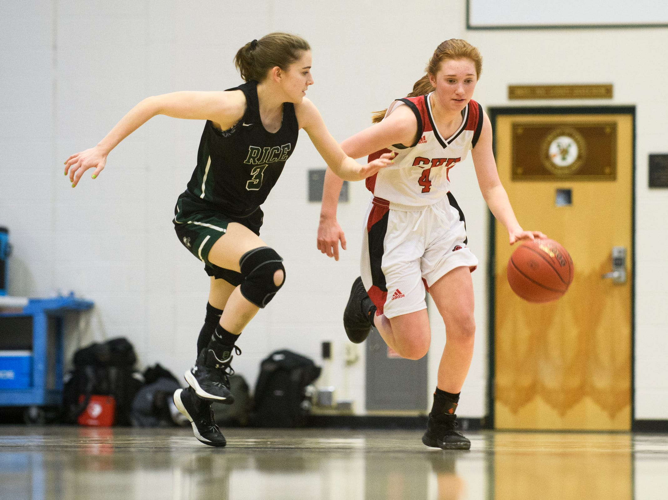 CVU's Catherine Gilwee (4) dribbles the ball down the court past Rice's Sadie Vincent (3) during the girls semifinal basketball game between the Rice Green Knights and the Champlain Valley Union Redhawks at Patrick Gym on Wednesday nigh March 6, 2019 in Burlington, Vermont.
