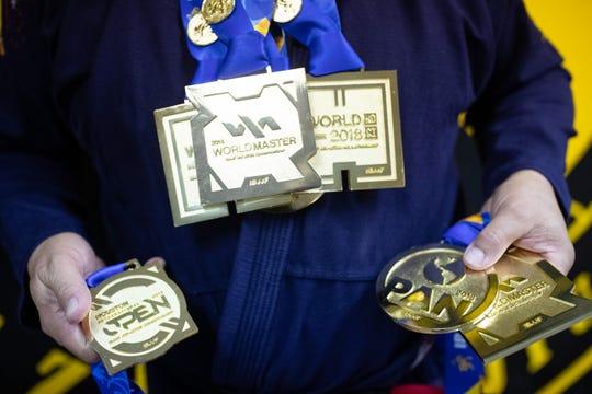John Barrera at Presa Brazilian Jiu-Jitsu puts on his double gold medal he won during the 2018 Pan-American Jiu-Jitsu Championship Jiu-Jitsu. Barrera 57-years-old won double gold at the Pan-American Jiu-Jitsu Championship in 2018.