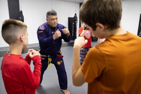 John Barrera shows a group of kids a punching combination as he helps instruct a Jiu-Jitsu class at Presa Brazilian Jiu-Jitsu on Wednesday, March 7, 2019. Barrera won double gold at the Pan-American Jiu-Jitsu Championship in 2018.