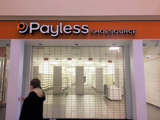 Shoppers pass a vacant Payless ShoeSource store at the Voorhees Town Center.