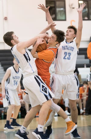 Cherokee's Anthony DiCaro, center, battles Freehold's Zach Barilka, left, for ball control during the Group 4 state semifinal boys basketball playoff game played at Egg Harbor Township High School on Wednesday, March 6, 2019.   Cherokee was defeated by Freehold, 44-42.