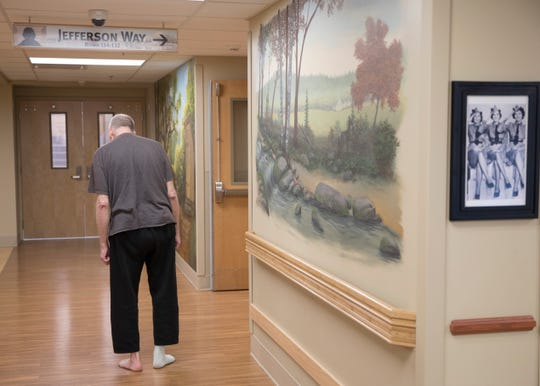 A patient at the Hopewell House walks down one of the hallways with one of the specialized murals recently finished to help residents feel less anxious.