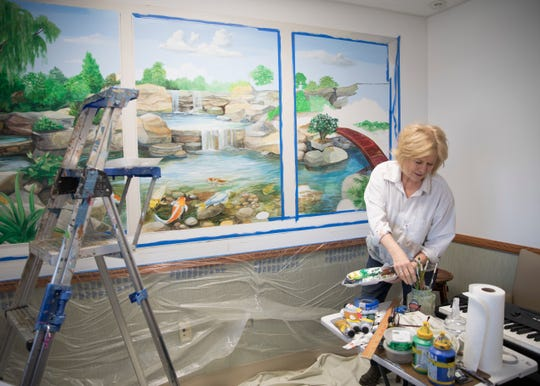 Artist Denise Ivey Telep works on finishing a mural at the Chillicothe VA Medical Center. Telep's father was a veteran and understands the special care that many veterans need.