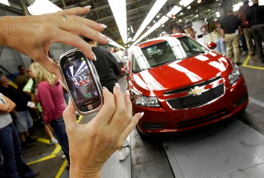 In this file photo, an auto worker takes a photo of the first Chevy Cruze compact sedan to come off the assembly line in Lordstown on Sept. 8, 2010.