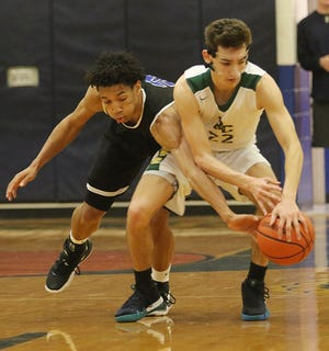 Denver Anglin of GSB reaches in to get the ball from Richie Greaves of Roselle Catholic.