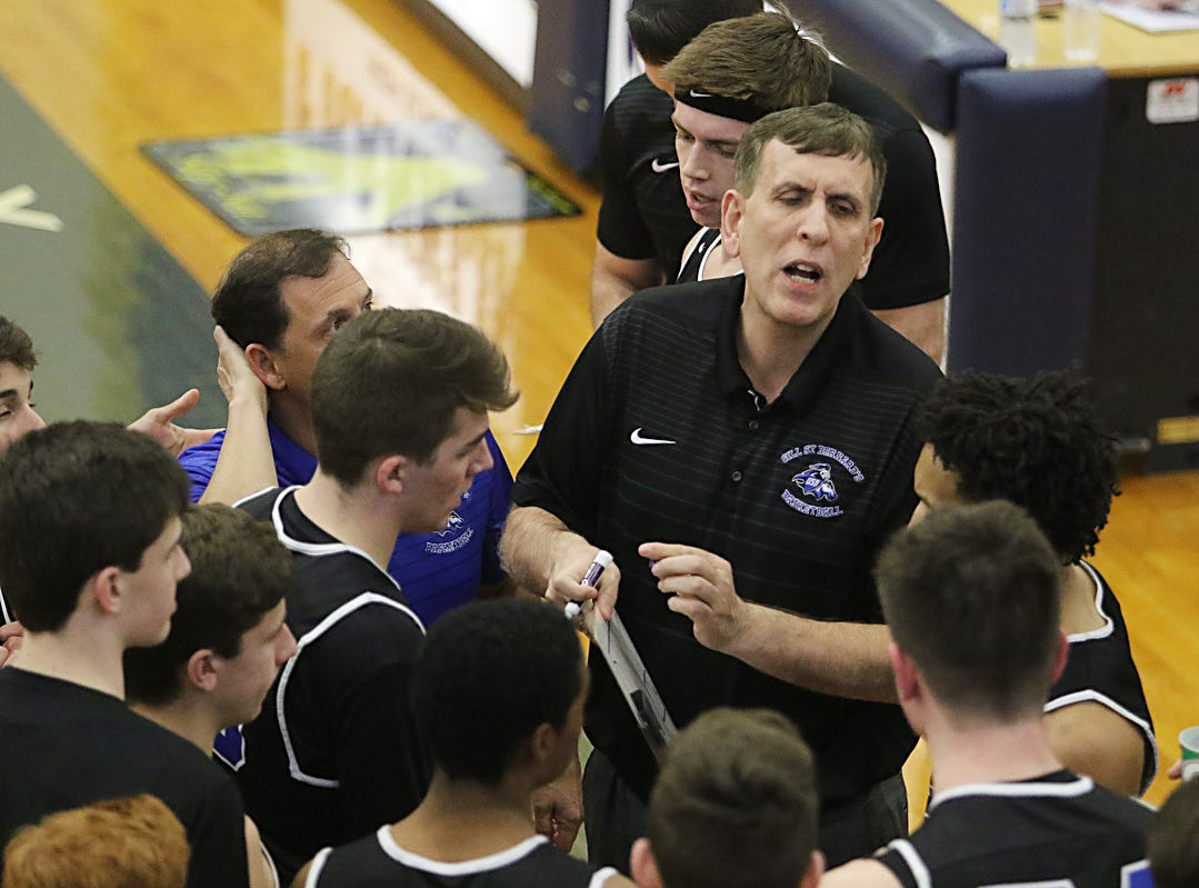 Gill St. Bernard's coach Mergin Sina talks to his players during a first half timeout.