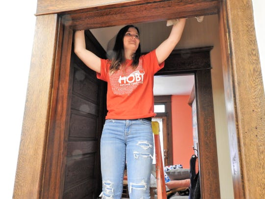 Lindsey Ashcraft of the River View High School National Honor Society cleans woodwork as a community service project at Rose of Sharon Retreat. The business is getting ready for a quilt retreat featuring people coming in from several states.