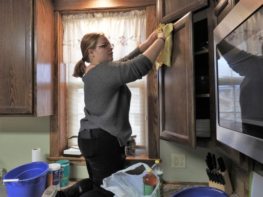 Cheyenne Hutton of the River View High School National Honor Society cleans cabinets as a community service project at Rose of Sharon Retreat. The business is getting ready for a quilt retreat featuring people coming in from several states.