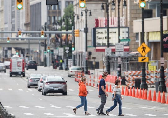 People are seen crossing Woodward Avenue near Montcalm Street in downtown Detroit.