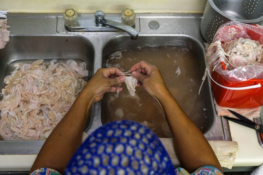 A worker in Detroit cleans chitlins in a sink earlier this year. The dish will be celebrated in South Carolina, as it is annually, this weekend.