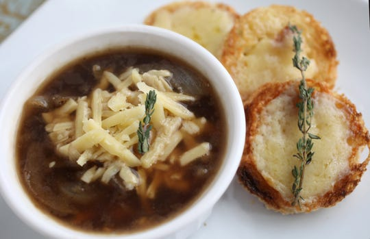 Guinness Onion Soup is topped with cheddar.