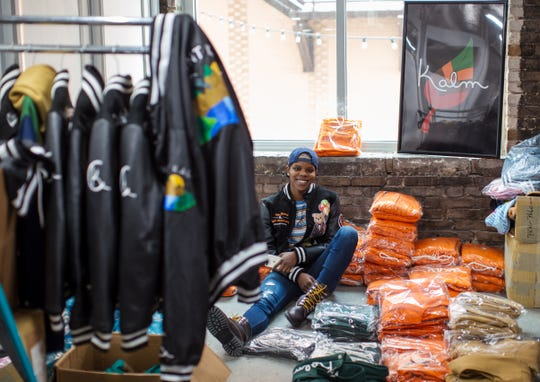 """Kiara Tyler, CEO/Founder, Kalm Clothing poses for a photo amongst packages of apparel to inspect before delivering online orders from her office in The Ferris Wheel in downtown Flint on Wednesday, February 27, 2019. """"I decided to come home because I couldn't find a job, period. The information, training and coaching you'd normally get in business school I was able to get here in a couple months."""