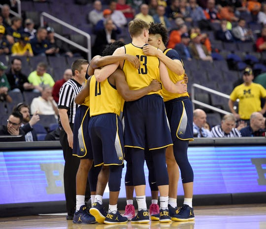 Michigan forward Moritz Wagner (13) and others huddle up before an NCAA college basketball game in the Big Ten tournament against Illinois, Thursday, March 9, 2017, in Washington. The team's flight to Washington was aborted on Wednesday because of airplane trouble, then rescheduled for Thursday morning. After dealing with the travel trouble, Michigan's players wore practice jerseys instead of normal game uniforms to face Illinois.