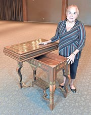 Linda Gratz poses with an 1800s Syrian game table.
