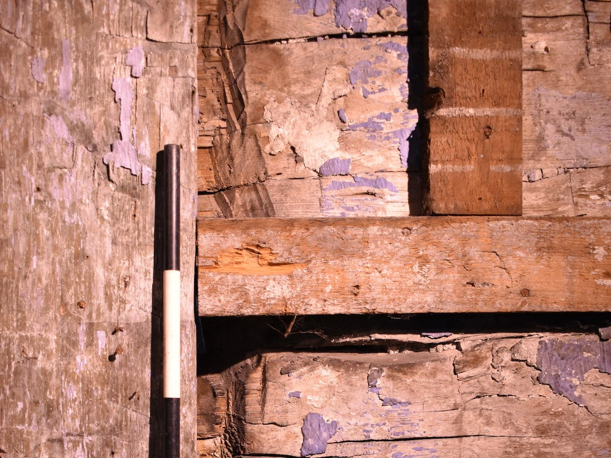 Inside, the most obvious sign of the original log cabin was a cross-section of the window in the front of the modern house, created by cutting through the cabin wall. The dark-and-white stick is known as a scale bar, and helps provide perspective and measurements.