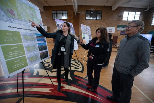 Alexa Bush, left, urban design director for the east region of the city of Detroit's Planning and Development department, talks about changes planned for Jayne Field with Shabina Chowdhury and Abdul Aziz Khandker .