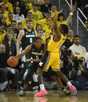 Michigan State's Cassius Winston works around Michigan's Zavier Simpson in the second half of the first meeting, won by MSU, in February.