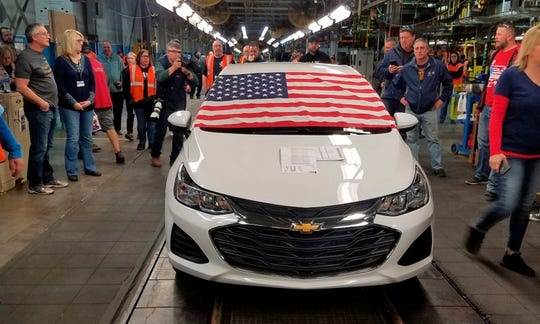 An American flag drapes the hood of the last Chevrolet Cruze as it comes off the assembly line at a General Motors plant where 1,700 hourly positions are being eliminated perhaps for good, on Wednesday, March 6, 2019, in Lordstown, Ohio. The factory near Youngstown is the first of five North American auto plants that GM plans to shut down by next year.