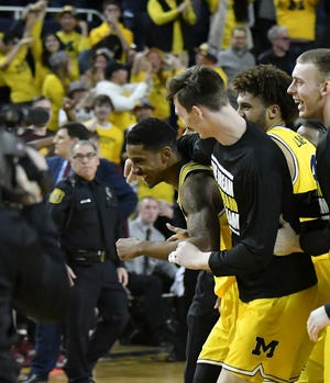 Players celebrate with Charles Matthews after he hits the winning shot against Minnesota on Jan. 22.
