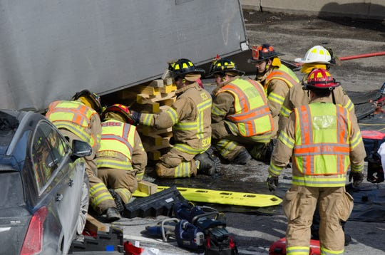 First responders work to free a woman trapped inside a car underneath a semi-truck on I-94 Thursday afternoon.