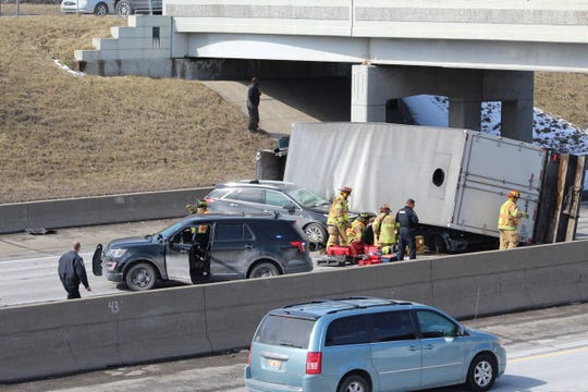 First responders work to free a woman trapped in her car underneath a tipped semi-truck on WB I-94 at 10 Mile Road.