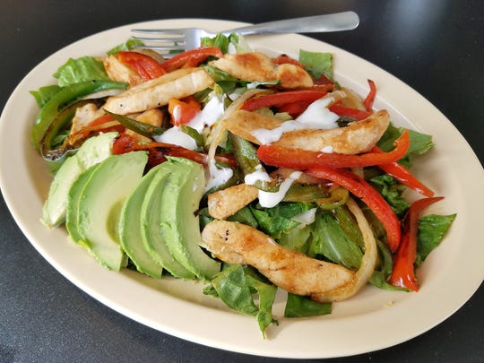 A chicken fajita salad with large, moist pieces of chicken and added avocado at Mele's Diner.