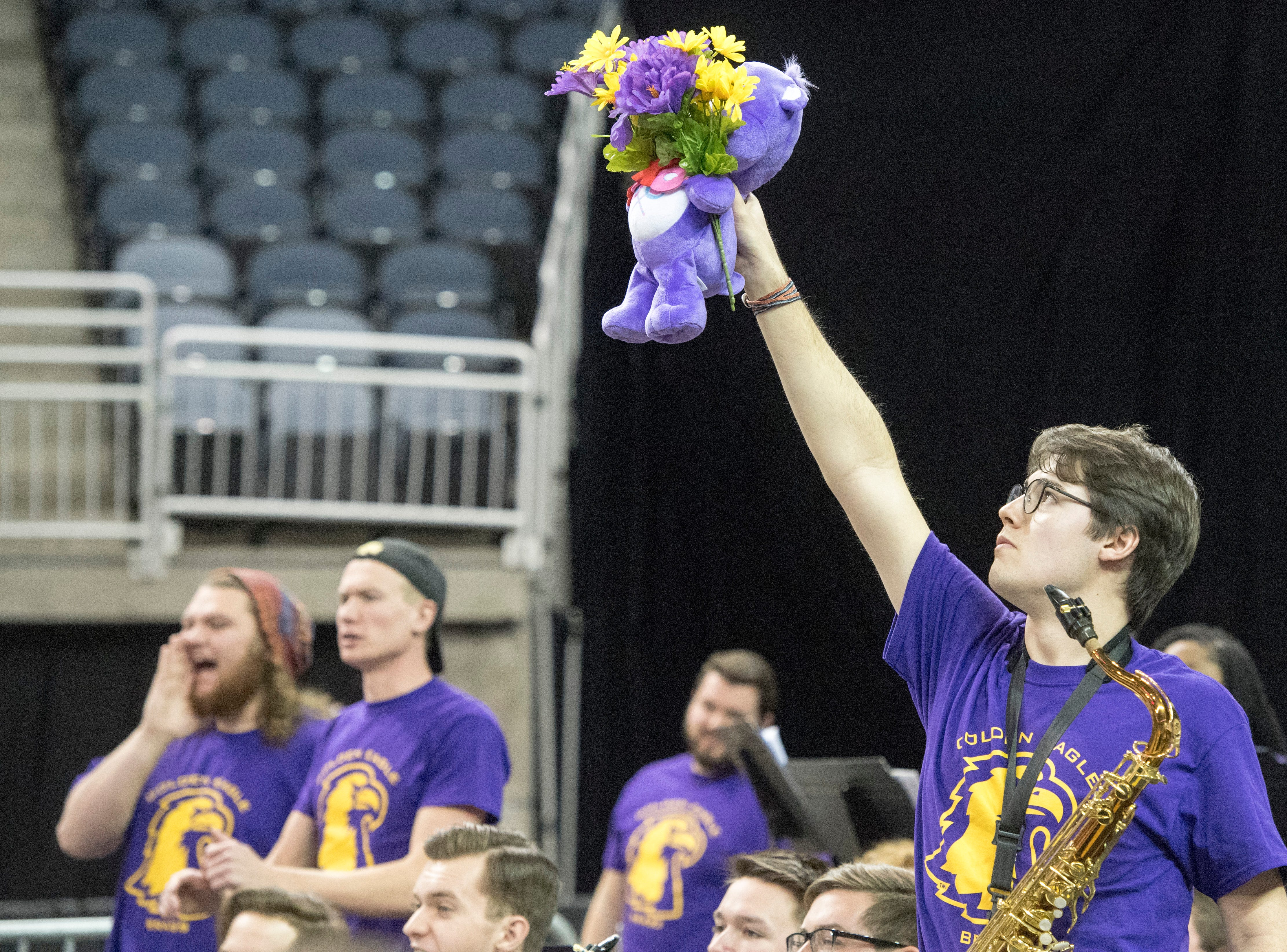 Tennessee Tech saxophone player Brandon Gilbert holds up a teddy bear with flowers to distract Austin Peay players at the free throw line during the Tennessee Tech vs Austin Peay game of the Ohio Valley Conference Tournament at the Ford Center in Evansville, Ind., Thursday, March 7, 2019.
