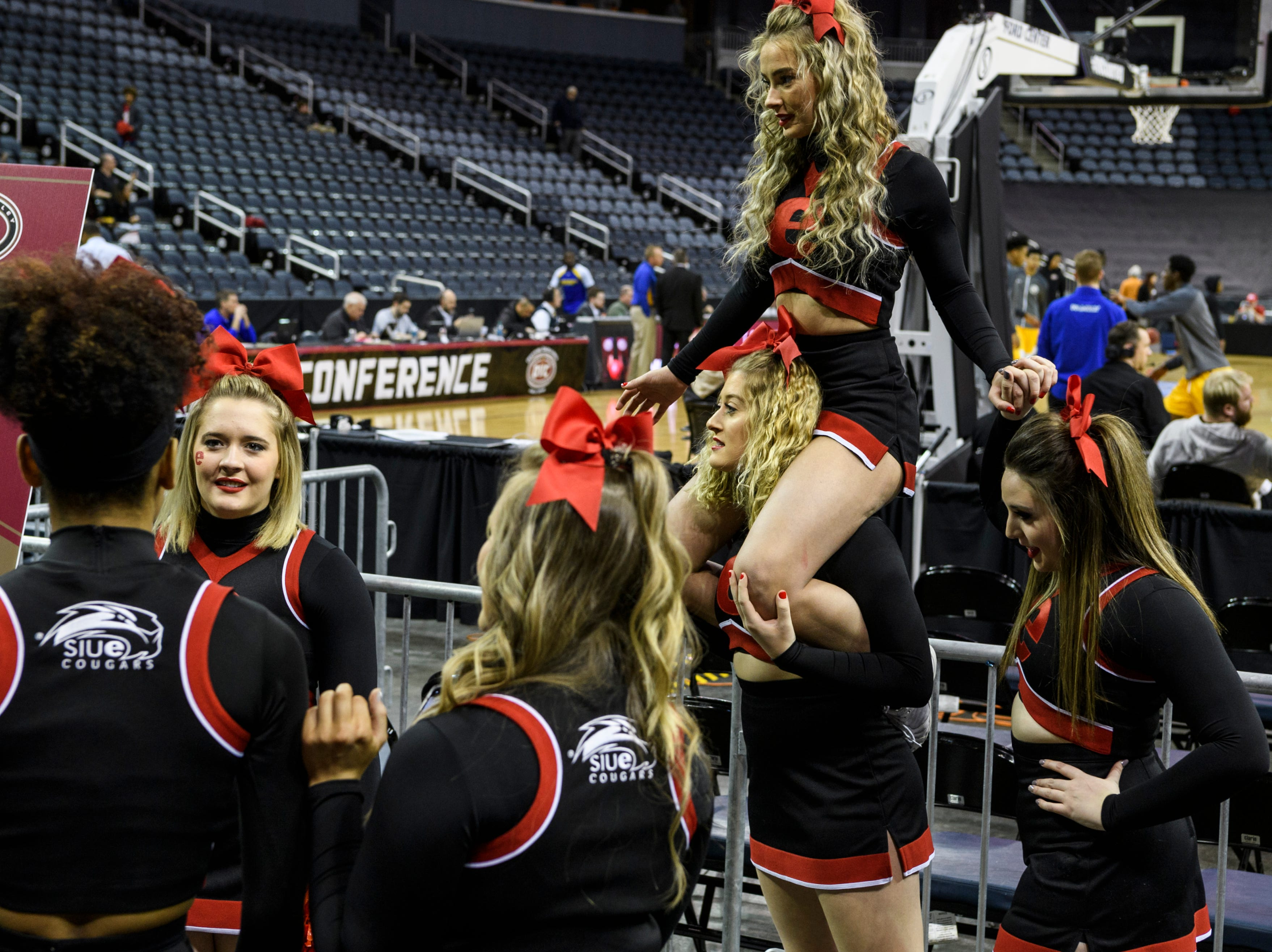 Cheerleaders, including Zoe Guilford balancing Ashley Pezzella on her shoulders, from the Southern Illinois University Edwardsville pass time talking and taking pictures together before the start of a first round Ohio Valley Conference tournament game at Ford Center in Evansville, Ind., Wednesday, March 6, 2019. Their mens basketball team lost to Morehead State, 72-68.