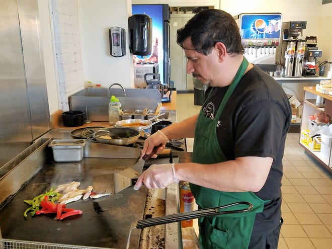Jorge Melendres begins a fajita salad with fresh peppers and chicken on the hot griddle at Mele's Diner.