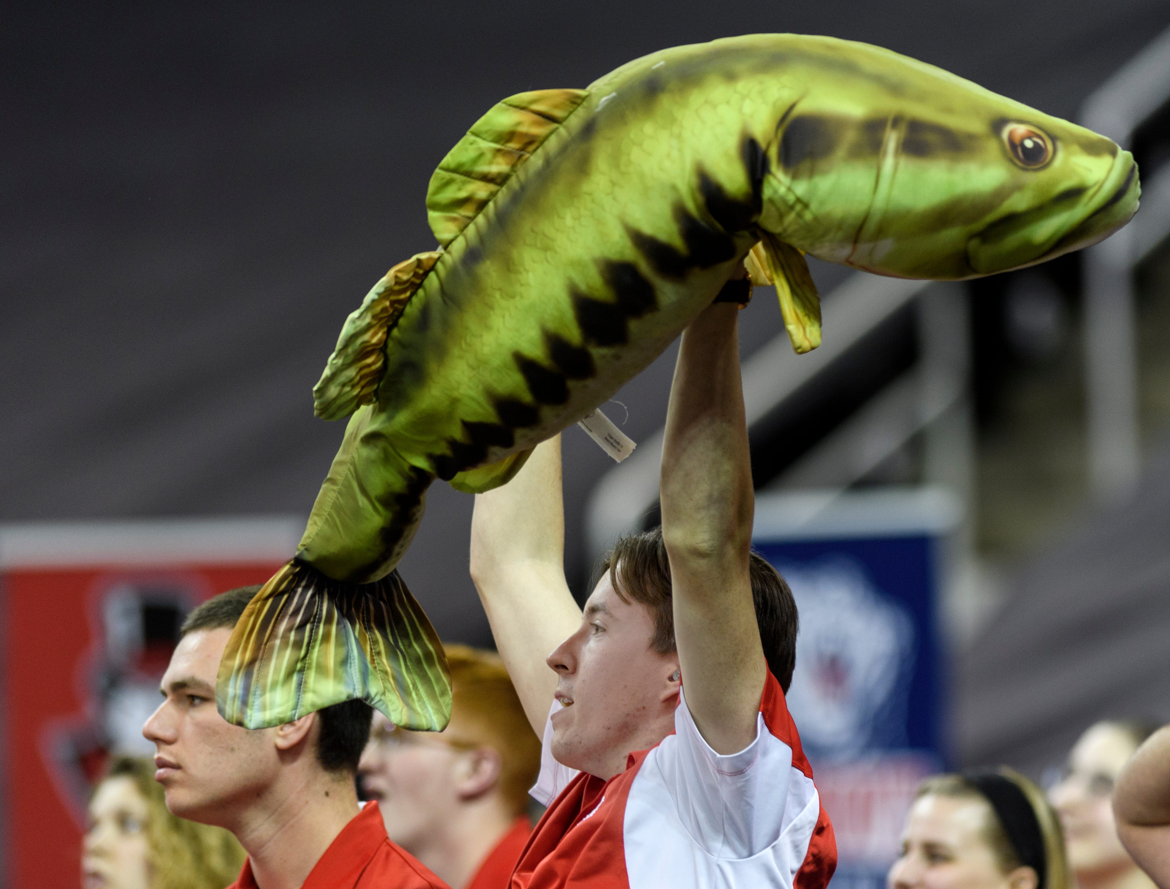 "Aaron Young, a member of the Belmont Blast pep band, holds up ""Bobby Fish,"" a plush fish named in honor of Belmont University President Robert Fisher during the women's basketball game against the Southeast Missouri Redhawks in the Ohio Valley Conference Tournament at Ford Center in Evansville, Ind., Wednesday, March 6, 2019. The pep band passes the fish around as they play music and cheer for their team."