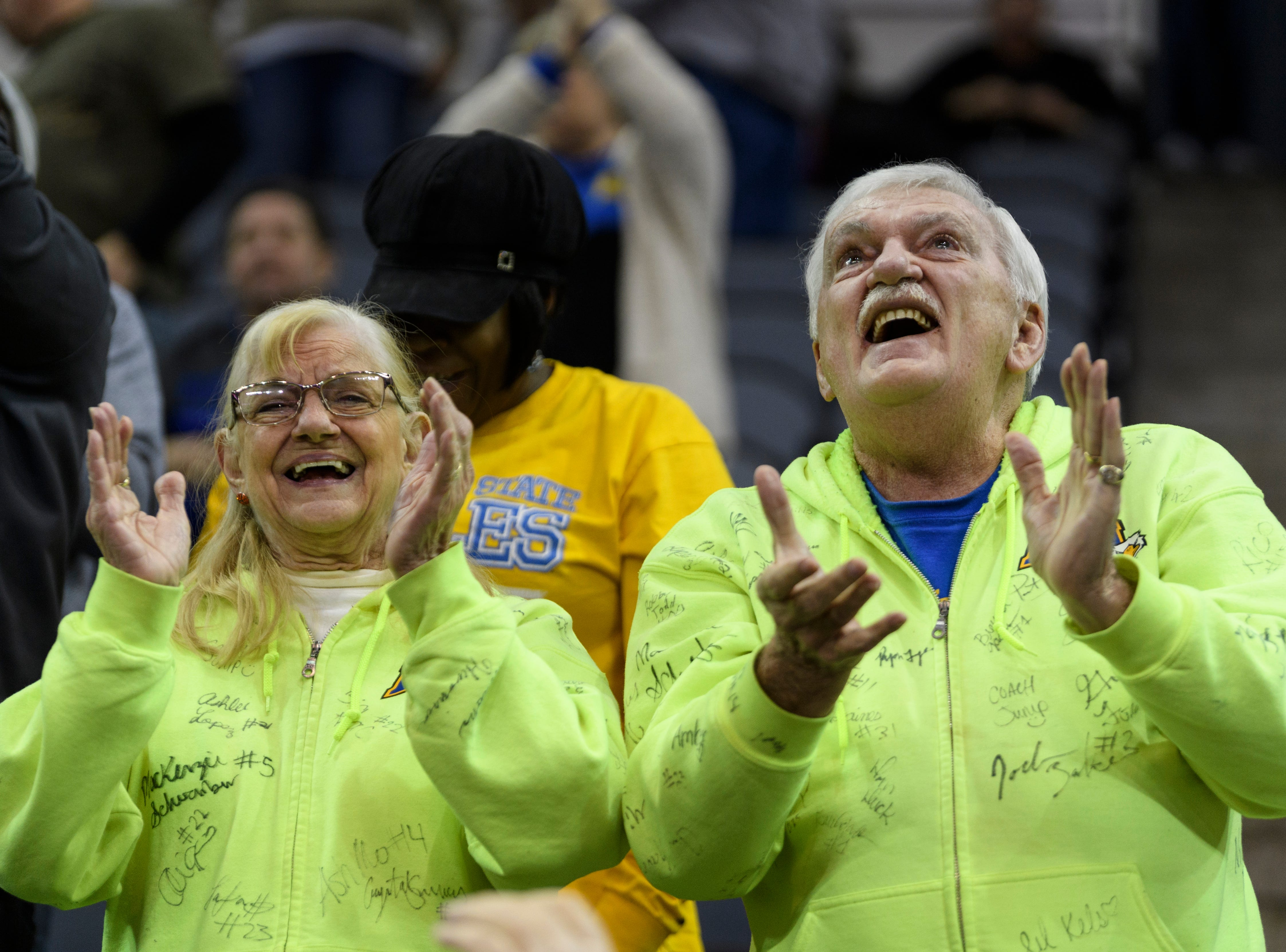 "Morehead State ""superfans"" Barbara and Rocky Niemeyer proudly cheer for the Morehead State men's basketball team after they defeated the Southern Illinois University Edwardsville Cougars in the first round of the Ohio Valley Conference Tournament at Ford Center in Evansville, Ind., Wednesday, March 6, 2019. The couple wore neon sweatshirts that has the name of every men's and women's basketball player from the past five years."