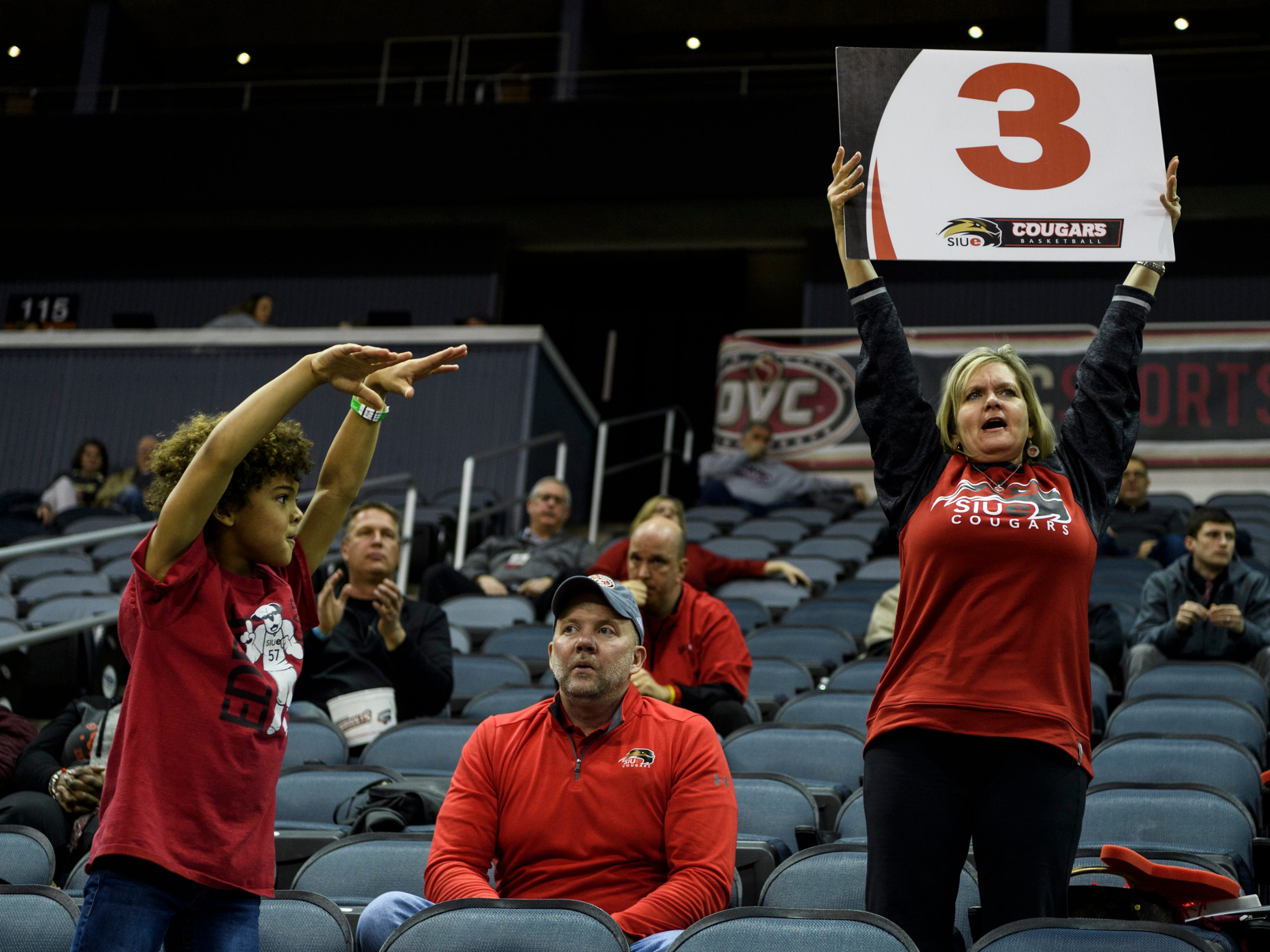 Jaxson Harris, 8, left, and Julie Lindenmeyer, right, cheer for the Southern Illinois University Edwardsville Cougars as Andy Lindenmeyer watches the game during the first round of the Ohio Valley Conference Tournament at Ford Center in Evansville, Ind., Wednesday, March 6, 2019. The Lindenmeyers' son Blake is a guard on the SIUE team.