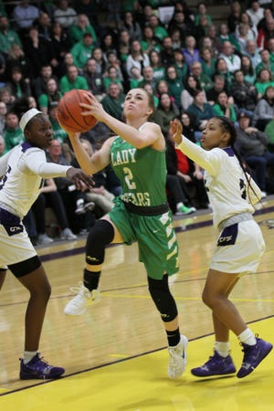 Margaretta's Jennah Yost splits two Africentric defenders to get to the basket.