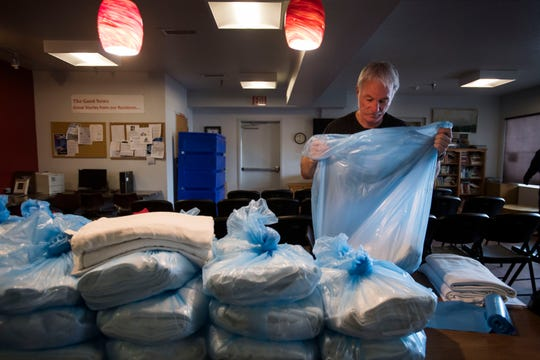 Mark, an employee at Catholic Charities, bags up fresh linens provided by Poudre Valley Hospital before opening for lunch on Thursday, March 7, 2019, at Catholic Charities of Larimer County in Fort Collins, Colo. The Mission, run by Catholic Charities, is commemorating its 30th anniversary this year.