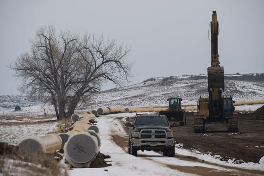 Pipeline construction crew members leave a worksite where sections of water pipeline have been strung out into place where they will be buried on Wednesday, March 6, 2019, near Longmont, Colo.