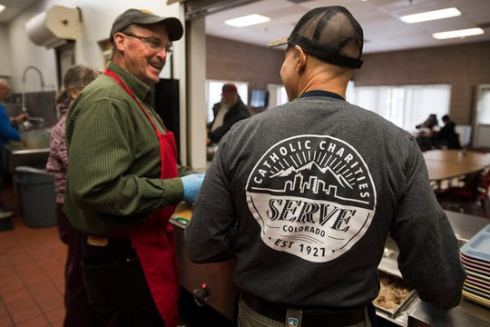 Volunteer Mike Sokol, right, and Cliff Considine share a laugh as they prepare to serve lunch to guests on Thursday, March 7, 2019, at Catholic Charities of Larimer County in Fort Collins, Colo.