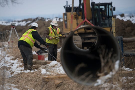 Pipeline construction crew members use a holiday tester to check the integrity of polyurethane coating on the outside of a section of pipe before setting it into place on Wednesday, March 6, 2019, near Longmont, Colo.