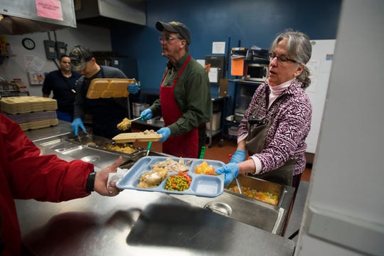 Volunteer Judy Wathen hand a lunch of Turket, mashed potatoes, vegetables and fruit to a guest during lunch on Thursday, March 7, 2019, at Catholic Charities of Larimer County in Fort Collins, Colo.