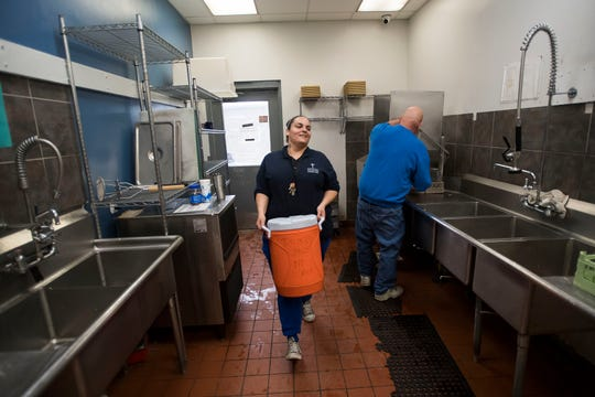 Assistant kitchen coordinator Yvette Muniz carries a cooler of milk in to be served to guests with lunch on Thursday, March 7, 2019, at Catholic Charities of Larimer County in Fort Collins, Colo.