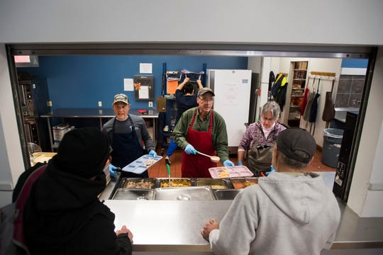 Volunteers, from left, Mike Sokol, Cliff Considine and Judy Wathen serve a lunch of turkey, mashed potatoes, fruit and vegetables to guests on Thursday, March 7, 2019, at Catholic Charities of Larimer County in Fort Collins, Colo.
