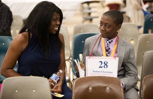 Awa Cham encourages her son Nelson Cherenfant during a break in the Lee County Spelling Bee on Wednesday at Three Oaks Middle School in Fort Myers. Nelson attends Veterans Park Academy of the Arts.