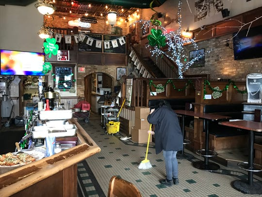 A Nicky's Lionhead employee sweeps up the bar area on Thursday, two days after a fire damaged part of the historic bar and restaurant. The bar will re-open on March 8.