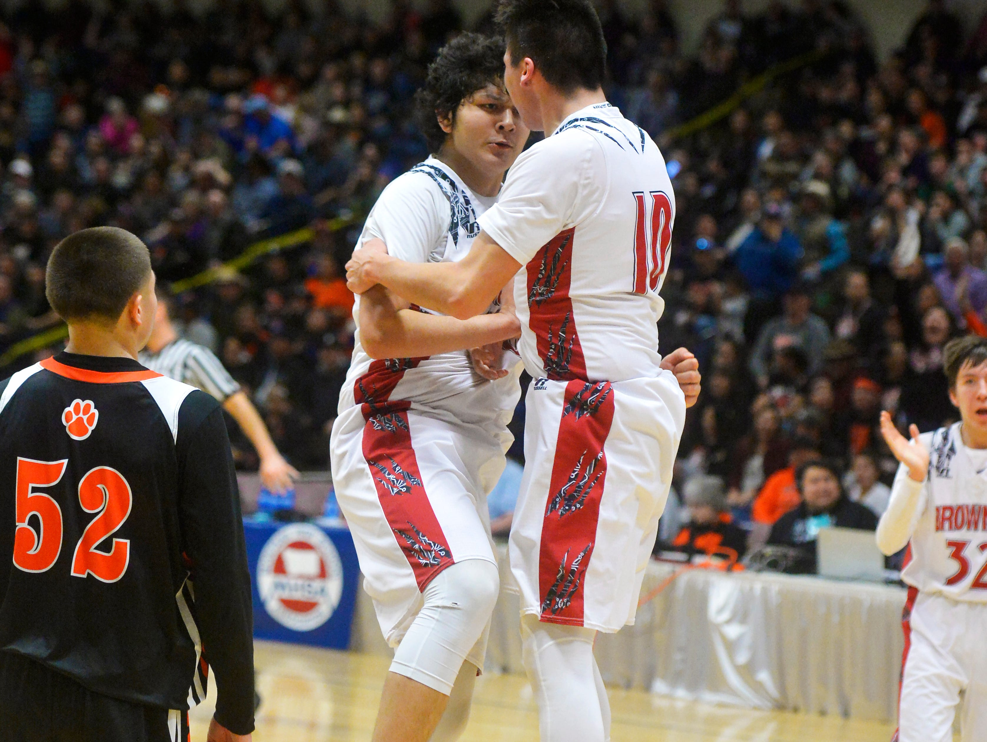 Browning's Tyree Whitcomb, left, and Riley Spoonhunter celebrate a buzzer beating three pointer to end the first half of Thursday's game against Hardin during the Class A State Basketball Tournament in the Four Seasons Arena.