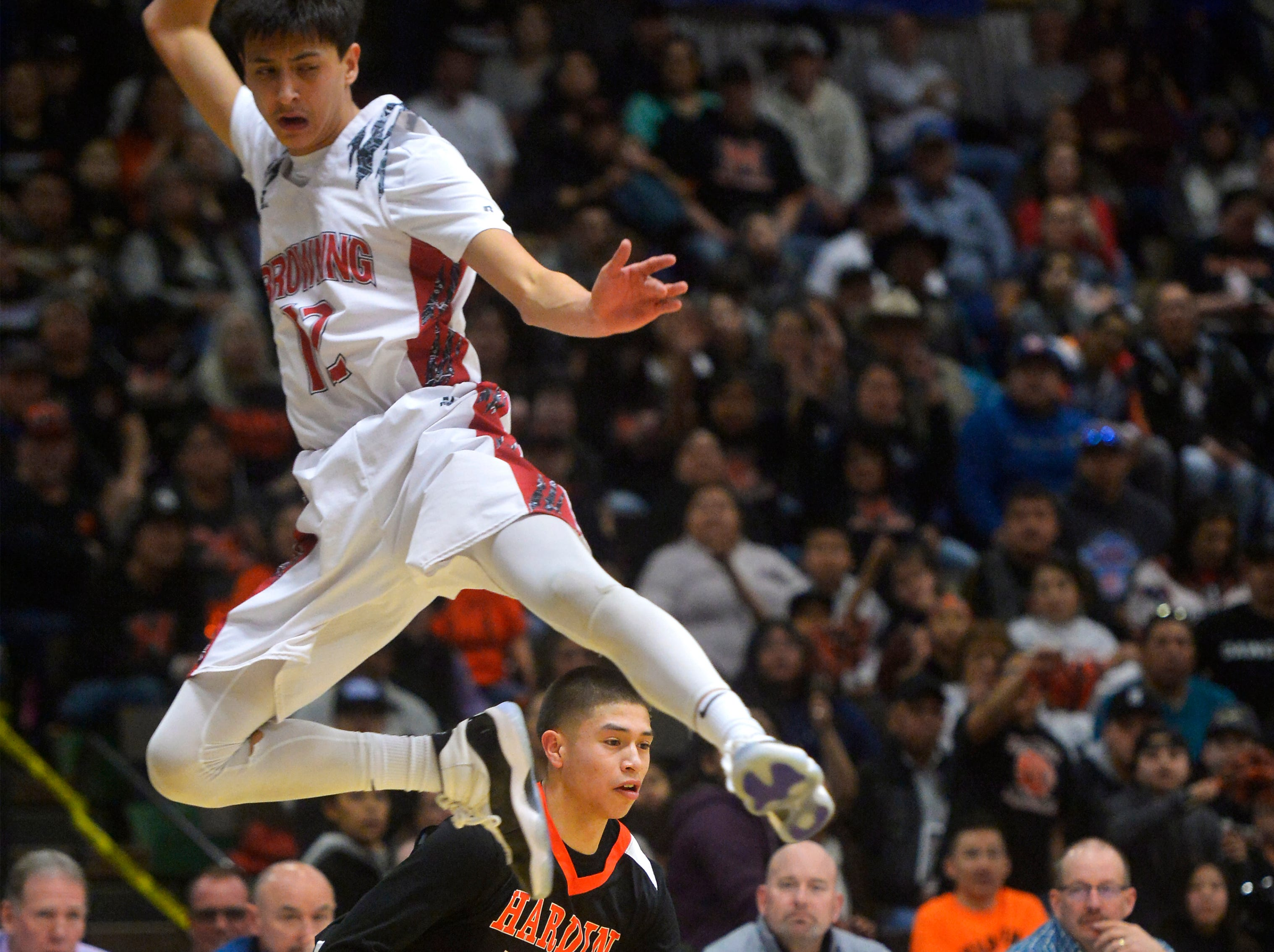 Hardin's Famous Lefthand gets by Browning's Ethan Running Crane on a head fake during the Class A State Basketball Tournament in the Four Seasons Arena, Thursday.