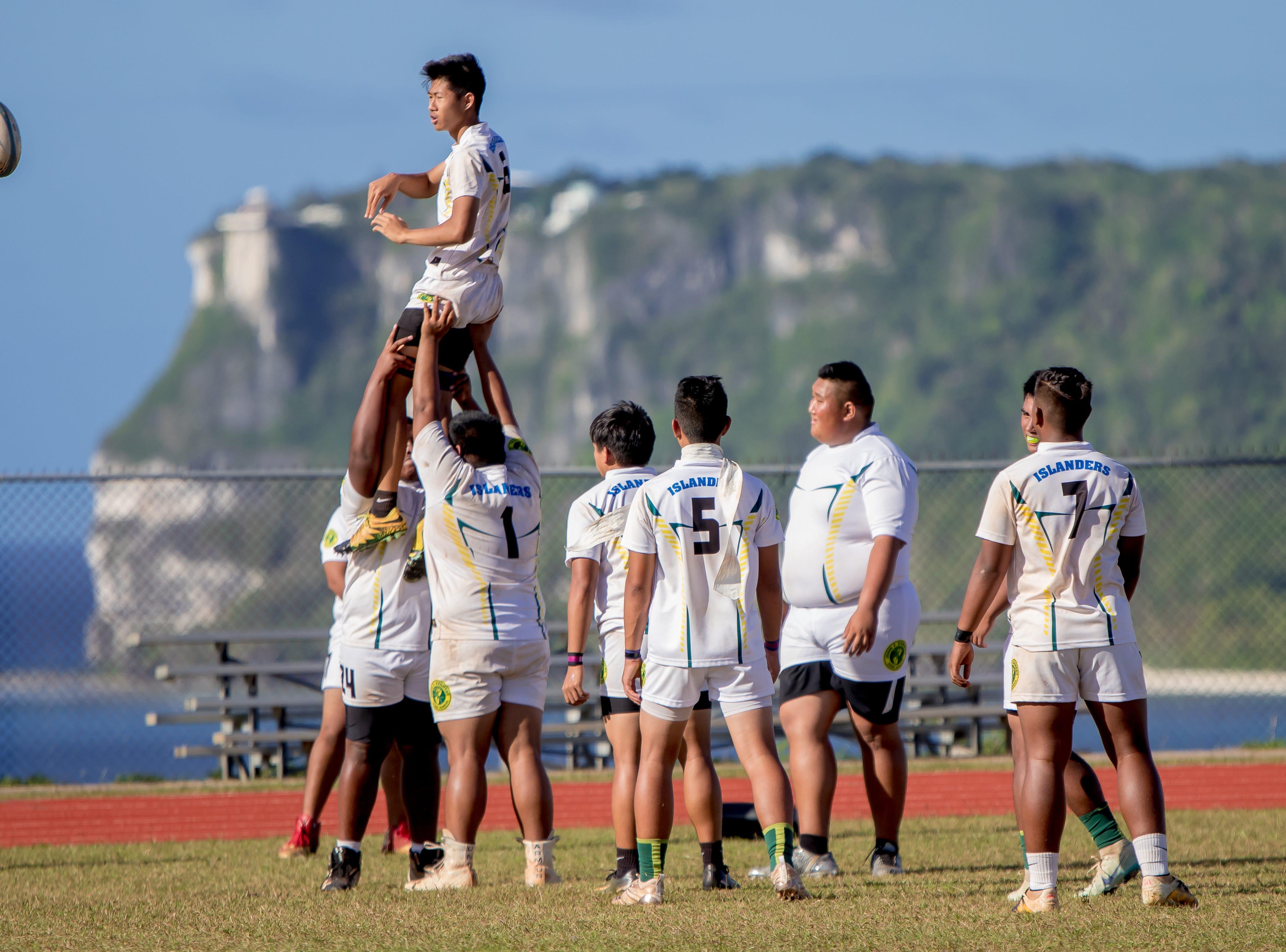 John F. Kennedy High School rugby players warm up for a match against Okkodo High School in an IIAAG/GRFU Boys Rugby match at Ramsey Field on March 6.