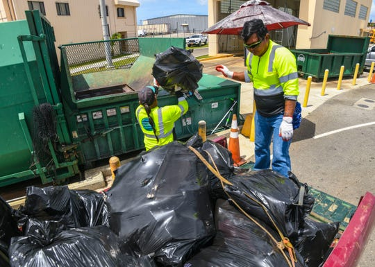 Guam Solid Waste Authority sanitation workers Gerald Castro, front, and Paul Duenas, help to unload bags of household trash from a customer's vehicle and into a compactor bin at the Harmon Residential Transfer Station on Thursday, March 7, 2019.