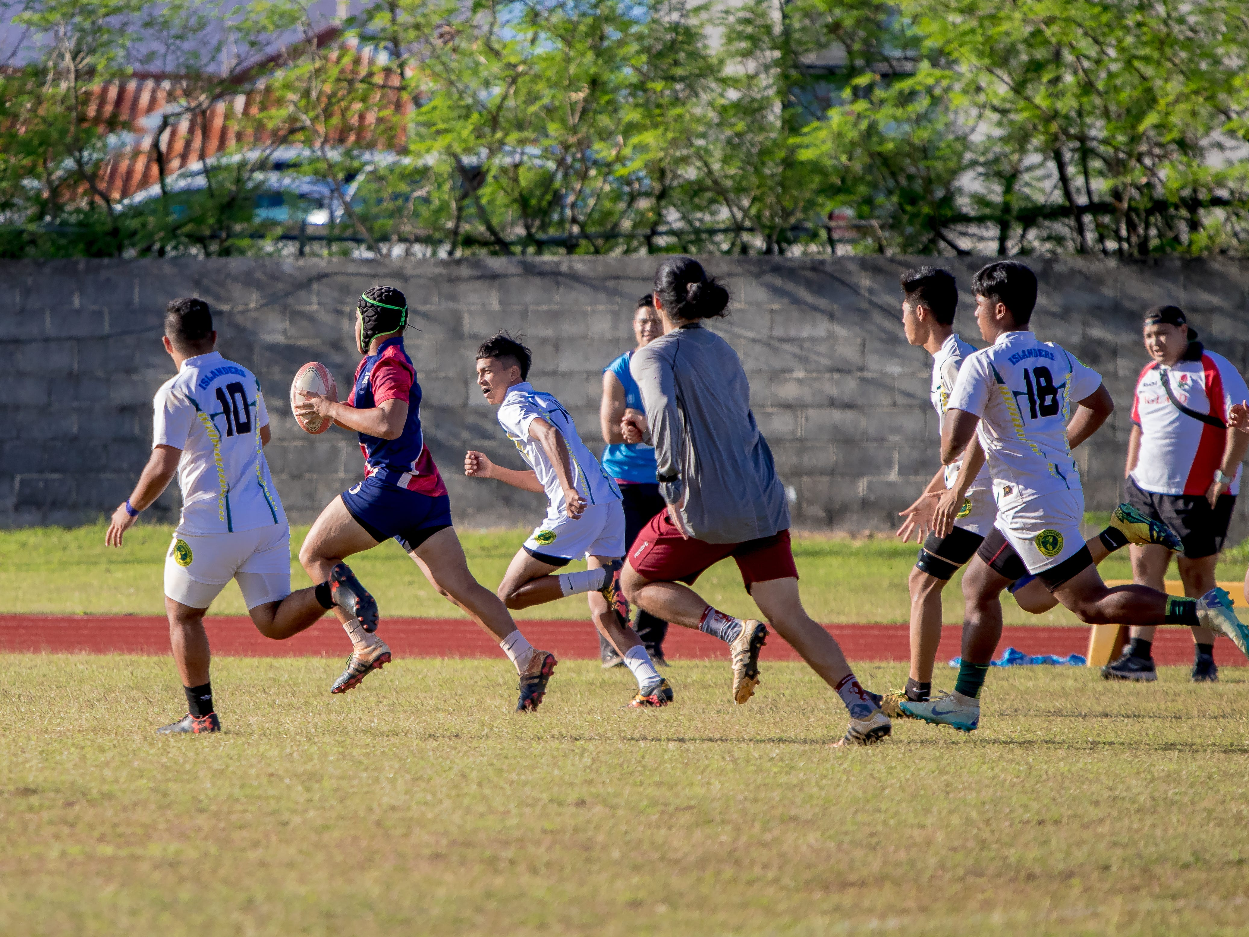 An Okkodo High School player attempts to evade the John F. Kennedy High School defenders during an IIAAG/GRFU Boys Rugby match at Ramsey Field on March 6.